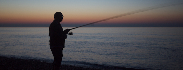 Fishing at sunset on Seaford beach, East Sussex.