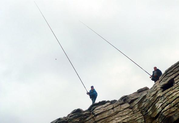 Pescadores practicando la pesca de lubina a corcho.