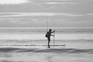 Pescador sobre tabla de paddle surf